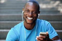 Kerel die mobiele telefoon houden luisterend aan muziek op hoofdtelefoons stock afbeelding