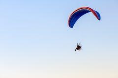 Kerel die op de duidelijk blauwe hemel door paramotor vliegen Royalty-vrije Stock Afbeeldingen