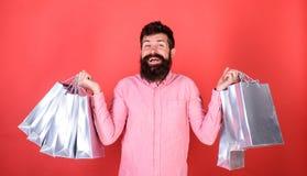 Kerel die op verkoopseizoen winkelen met kortingen De mens met baard en snor houdt het winkelen zakken, rode achtergrond Verkoop  stock foto's