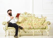 Kerel die oud boek met plezier lezen De mens met baard en snor zit op barokke stijlbank, houdt boek, witte muur royalty-vrije stock afbeelding