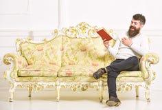 Kerel die oud boek met plezier lezen De mens met baard en snor zit op barokke stijlbank, houdt boek, witte muur stock afbeelding