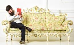 Kerel die oud boek met plezier lezen Humoristisch literatuurconcept De mens met baard en snor zit op barokke stijlbank royalty-vrije stock afbeelding
