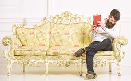 Kerel die oud boek met plezier lezen Humoristisch literatuurconcept De mens met baard en snor zit op barokke stijlbank royalty-vrije stock foto
