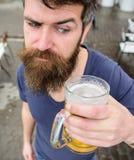 Kerel die rust met koud bier van het vat hebben Bier van het vatconcept De mens met baard en snor houdt glas met bier terwijl Stock Fotografie