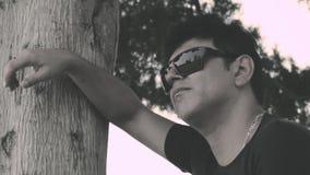 Kerel die tegen een boom wordt geleund stock video