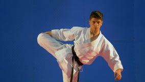 Kerel die vechtsportenkimono dragen die zijn spieren aan het begin van zijn routine opleiding uitrekken stock video
