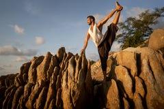 Kerel die yoga doen bij zonsondergang door het overzees stock foto