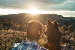 Kerel die zijn hond affectionately koesteren royalty-vrije stock foto's