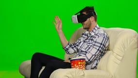 Kerel in een masker vergroot werkelijkheidsapparaat Het groene scherm stock footage