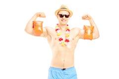 Kerel in een zwempak met zwemmende wapenbanden die zijn spieren tonen Royalty-vrije Stock Afbeelding