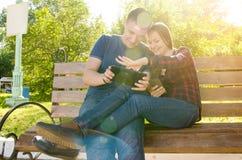 Kerel en glimlachend meisje die op hun foto's op de tablet letten stock foto's