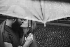 Kerel en het meisje die onder een paraplu kussen Royalty-vrije Stock Foto