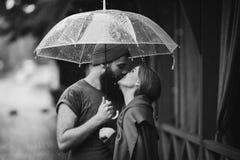 Kerel en het meisje die onder een paraplu kussen Stock Foto