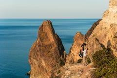 Kerel en meisje bij het overzees die op de rand van de klip koesteren stock fotografie