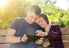 Kerel en meisje die bij de online opslag op de tablet winkelen stock afbeelding