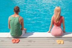 Kerel en meisje die dichtbij water rusten stock fotografie