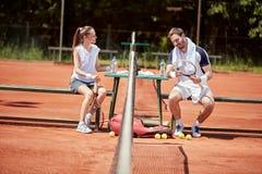 Kerel en meisje die op tennisbaan spreken stock foto's