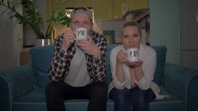 Kerel en meisje die op TV met mokkenm. en Mevr. letten 4K stock video