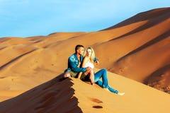 Kerel en meisje op de zandduinen in Sahara Desert Royalty-vrije Stock Foto
