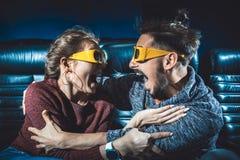 Kerel en meisjes zijn 3d glazen zeer ongerust gemaakt terwijl het letten van op een film royalty-vrije stock afbeeldingen