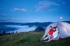 Kerel en meisjeszitting in tent bij dageraad met mening van mooi landschap royalty-vrije stock fotografie
