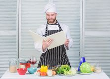 Kerel gelezen boekrecepten Culinair Kunstenconcept De mens leert recept Verbeter het koken vaardigheid De recepten van de boekfam stock afbeeldingen