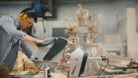 Kerel in glazen en hoofdtelefoons die hout met circulatzaag zagen in houten workshop stock footage