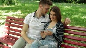 Kerel het letten op beelden in mobiele telefoon van zijn meisje op een bank stock footage