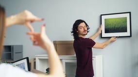 Kerel het plukken plaats voor beeld wanneer meisje dat kader met vingers maakt stock videobeelden
