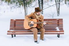 Kerel het spelen gitaar in park in de winter Stock Afbeelding