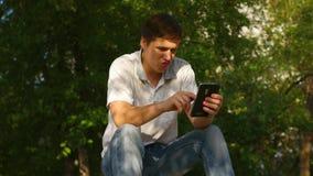 Kerel het spelen op smartphone stock footage