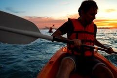 Kerel in kajaks in het overzees bij zonsondergang royalty-vrije stock afbeeldingen
