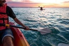 Kerel in kajaks in het overzees bij zonsondergang royalty-vrije stock foto
