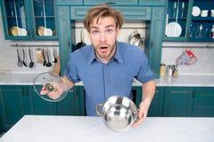 Kerel met de verraste open steelpan van de gezichtsgreep, deksel in keuken royalty-vrije stock afbeelding
