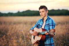 Kerel met een gitaar speelliederen bij zonsondergangaard royalty-vrije stock foto