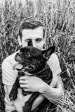 kerel met een hond voor een gang, een Franse buldog in de handen van een mens Stock Foto's