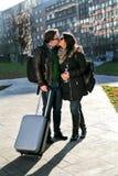 Kerel met een koffer en meisjeskussen in park Stock Fotografie