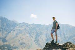 Kerel met een reisrugzak op de bovenkant van een kei Stock Foto
