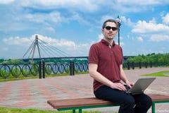 Kerel met laptop in het park stock afbeelding