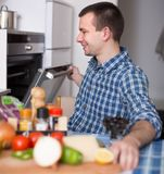 Kerel met oven in de keuken stock fotografie