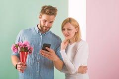 Kerel met telefoon en boeket van bloemen, pastelkleur roze en groene achtergrond Romantisch concept De mens toont foto op smartph royalty-vrije stock afbeelding