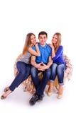 Kerel met twee meisjes die op de laag zitten Stock Foto's