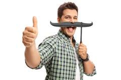Kerel met valse snor die een duim op gebaar maken Stock Afbeeldingen