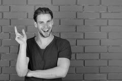 Kerel met varkenshaar in donkerblauwe t-shirt, exemplaarruimte De macho met het glimlachen gelukkig gezicht houdt vinger tegen stock afbeelding