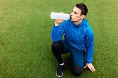 Kerel na oefening, drinkwater op het voetbalgebied Portret van mooie Kerel in sportkleding royalty-vrije stock afbeelding