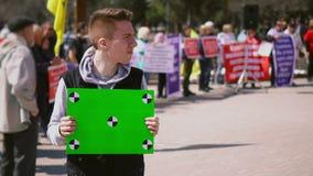 Kerel op de chroma zeer belangrijke lijst van de demonstratie bevindende greep Affiche met punttellers stock footage