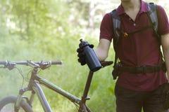 Kerel op een fiets met een fles in openlucht Stock Fotografie
