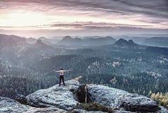 Kerel op een klip boven fee nevelige vallei Gebarsten Rots royalty-vrije stock foto