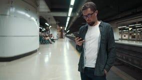 Kerel op een platform in metro met smartphone stock footage