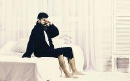 Kerel op slaperig gezicht die in ochtend opstaan Macho met baard en snor het trage ontspannen na dutje, rust Mens in robe stock afbeelding